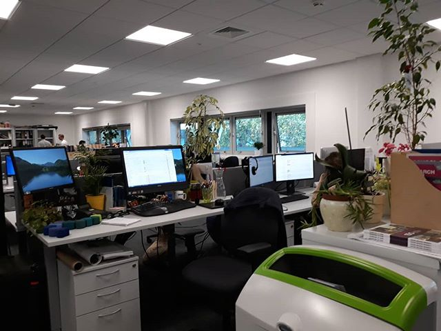 """Moved to my new office today with my greenhouse of plants, adjustable height desk, mini wall of the weird, and miniature ottoman chairs that @nickyanderton710 made. Back to open plan office after 9 years. Not since I left the lexicographer's """"morgue""""... #changeisgood"""